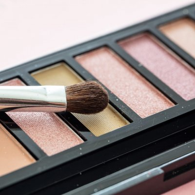 Eye shadow pallete kit against pink background, copy space